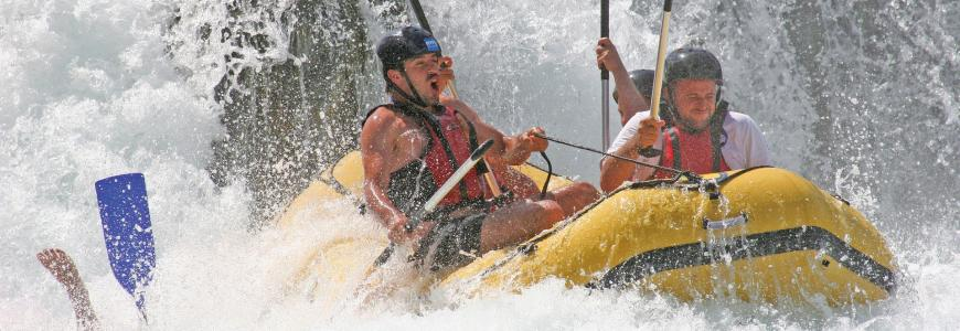 Photo of several people white water rafting and one person overboard with their paddle and foot in the air.